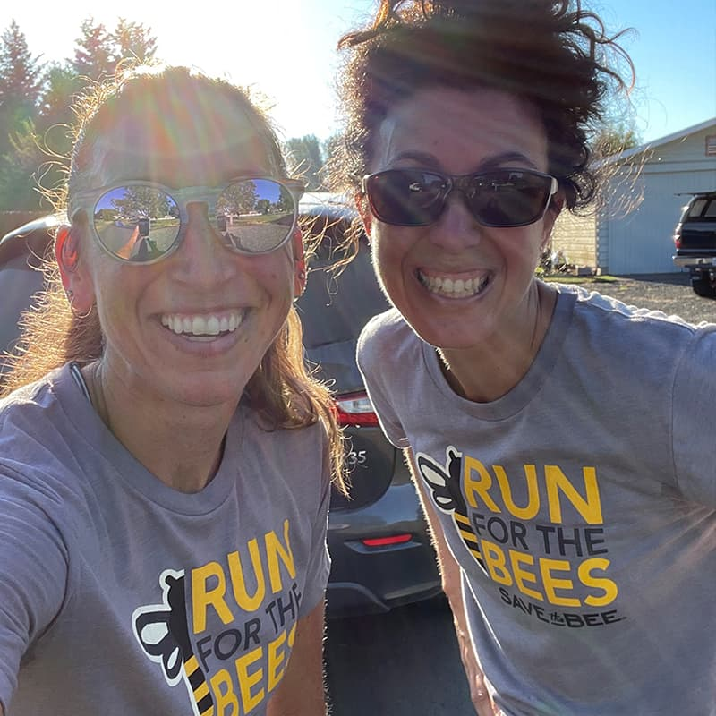 Two women in run for the bees shirts getting ready to run a 5k race