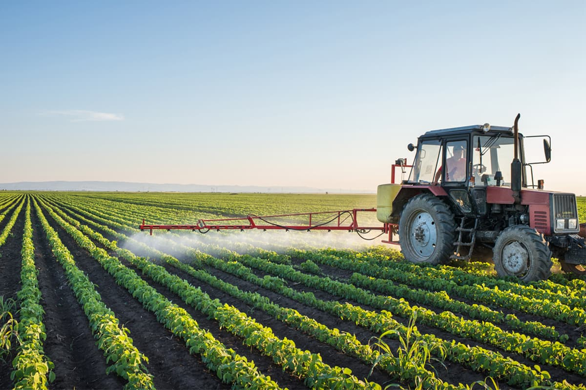 Tractor spraying field with presiticdg